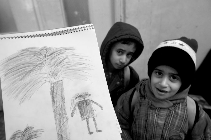 In Damascus, Syria, Iraqi refugee children show palm trees and smiling girl back home.