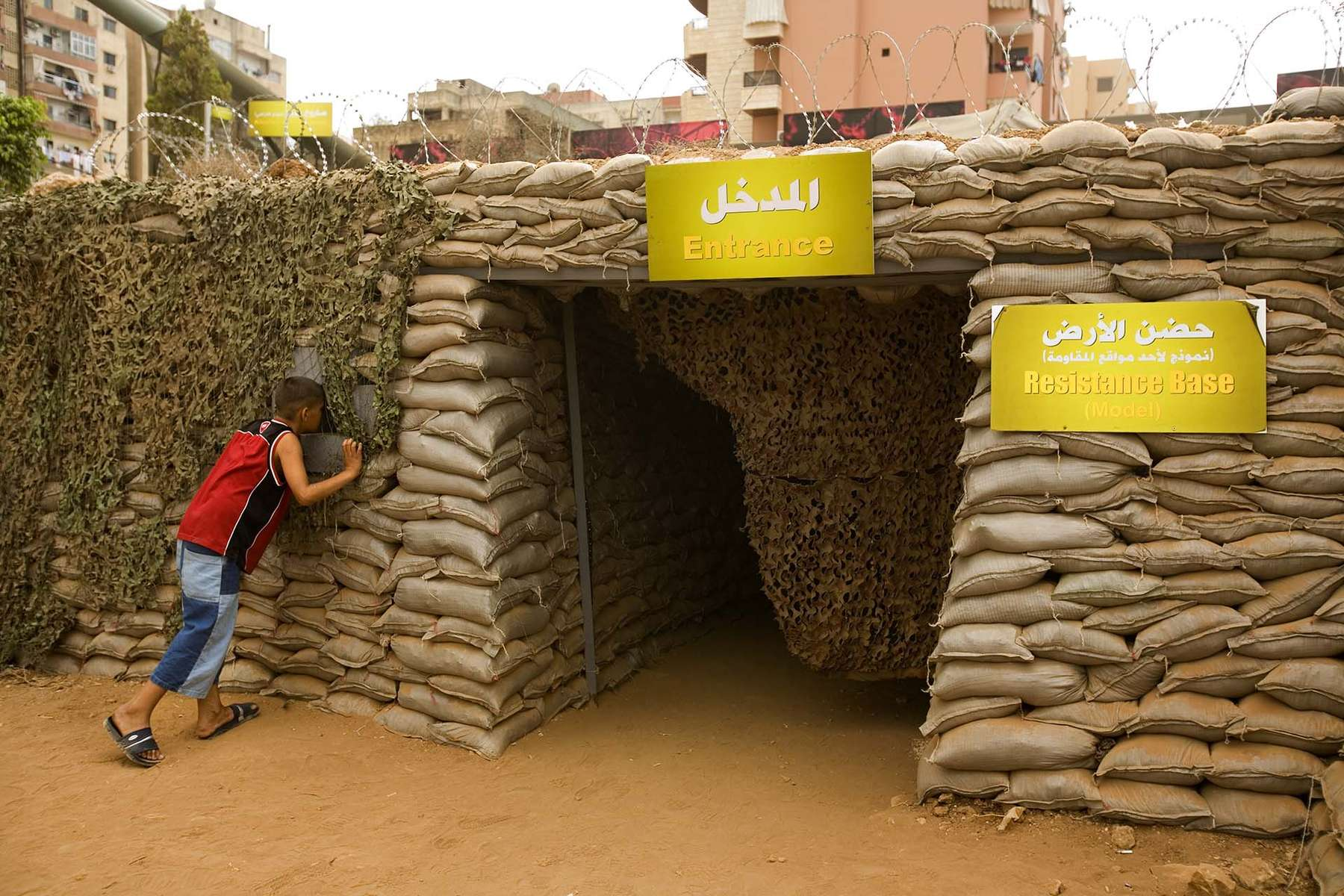 Lebanese boy peeks into makeshift bunker at the exhibit commemorating July War organized by Hezbollah which opened Tuesday, August 13, 2007, a day ahead of the end of July War in the southern suburb of Beirut. The exhibit features photographs, weapons, and audio visual shows.