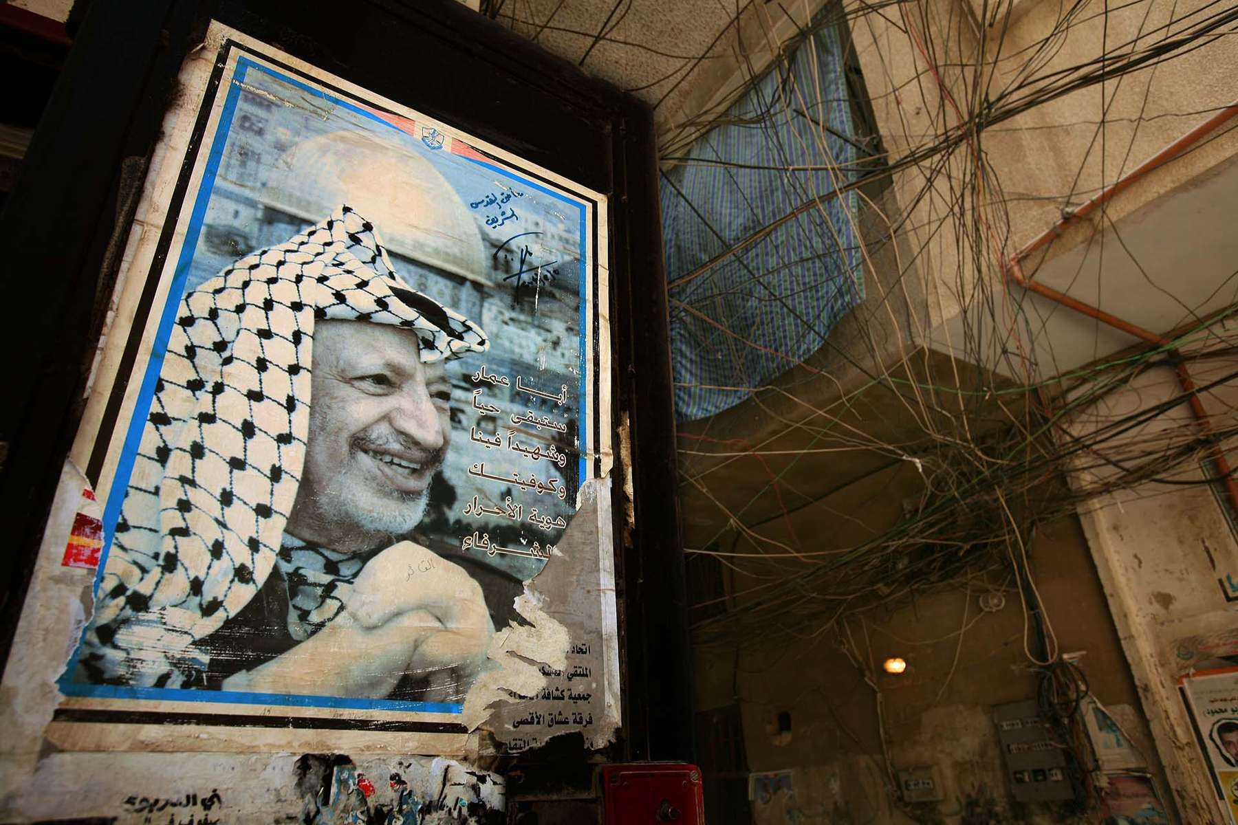 Poster of Yassar Arafat and a web of power cables at Baddawi Palestinian refugee camp near the city of Tripoli Saturday, May 26, 2007. Battle between Lebanese Army and Fatah al-Islam, armed Sunni Palestinian group thought to have links with al-Quida continue to fight continues at near-by Nahr Al-Bared camp. Fatah al-Islam started at Baddawi camp, but left the camp and moved to Baddawi to establish themselves.