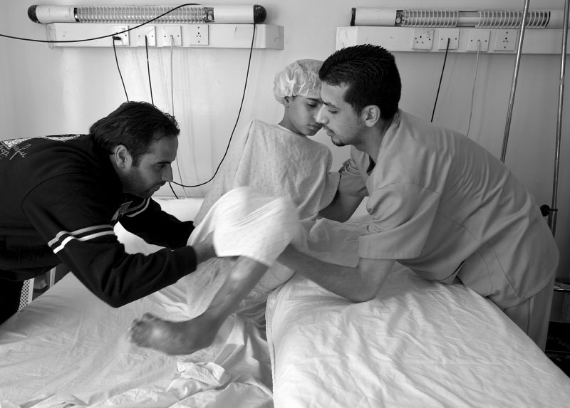 Faris and a nurse transfer his little brother Abdulla, an 11-year old boy from Baghdad, to a wheeled bed for surgery. He was walking through a crowded market in his neighborhood with his mother and aunt in May last year when an enormous car bomb explosion ripped through the market. His mother and aunt suffered minor injuries but Abdullah was not so lucky, and he was rushed to a near-by hospital. Doctors at the hospital were overwhelmed by serious injuries coming in and they could only give him emergency treatment. Abdullah's right arm and leg were amputated to save his life. His left foot received severe trauma from the bomb blast and it is curled up like a crab foot.  He was brought to Jordan for further reconstructive surgery.