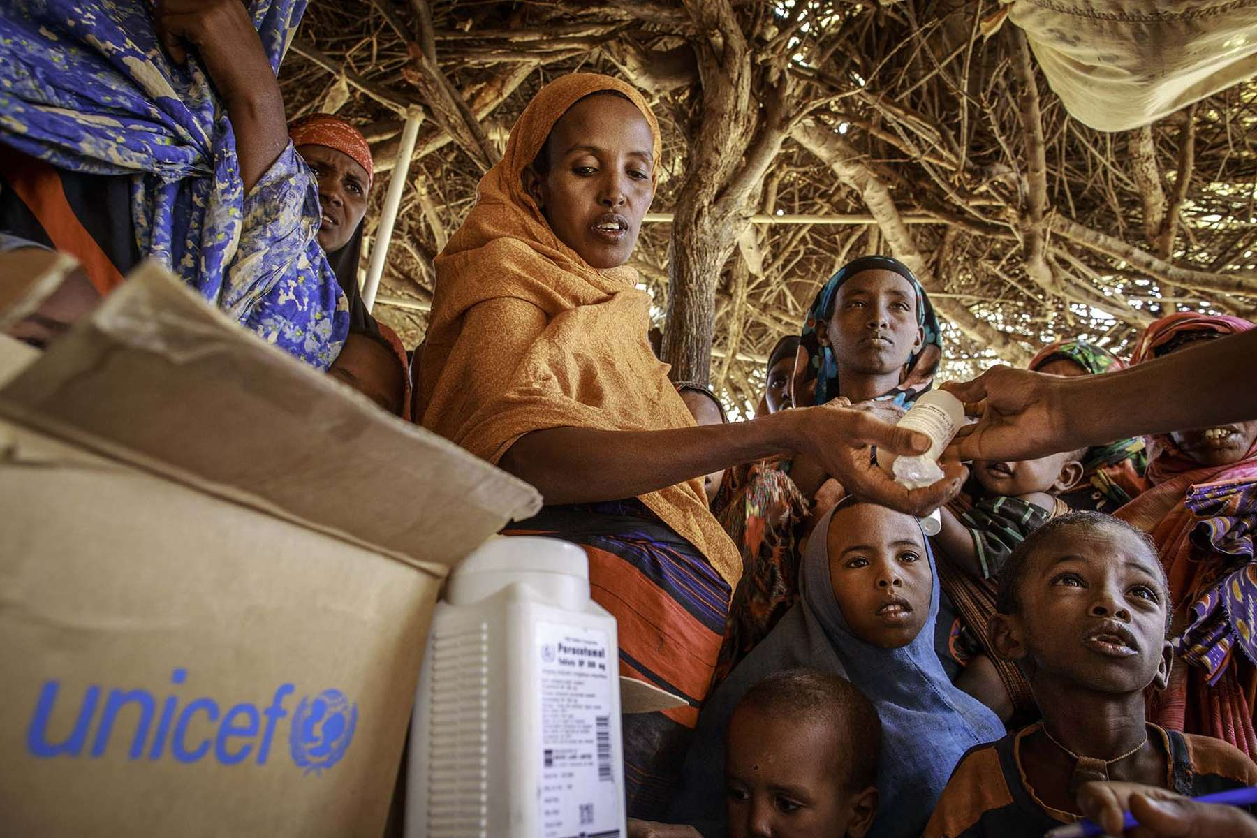 Young mother receives medication for his son at a mobile health crinic visiting her section in Kobe Refugee Camp in Somali Region of Ethiopia June 12 2012. The camp for Somali refugees is vast and they often do not come to health crinic, so the program is crated to reach out to impove the health of the refugees.