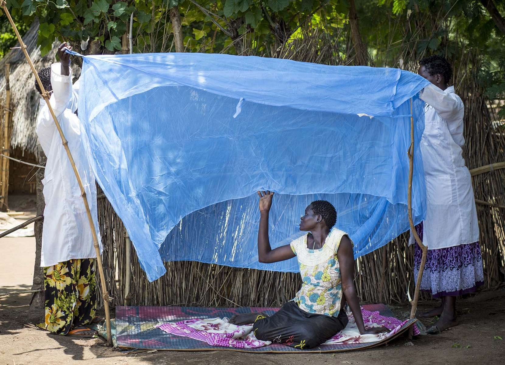 With the help of a pregnant woman, health extension workers Achang Objo, left, and Abang Obang, give a live demonstration of the proper use of mosquito net to the residents of Itang Woreda in Gambella State of Ethiopia 29 August 2013.