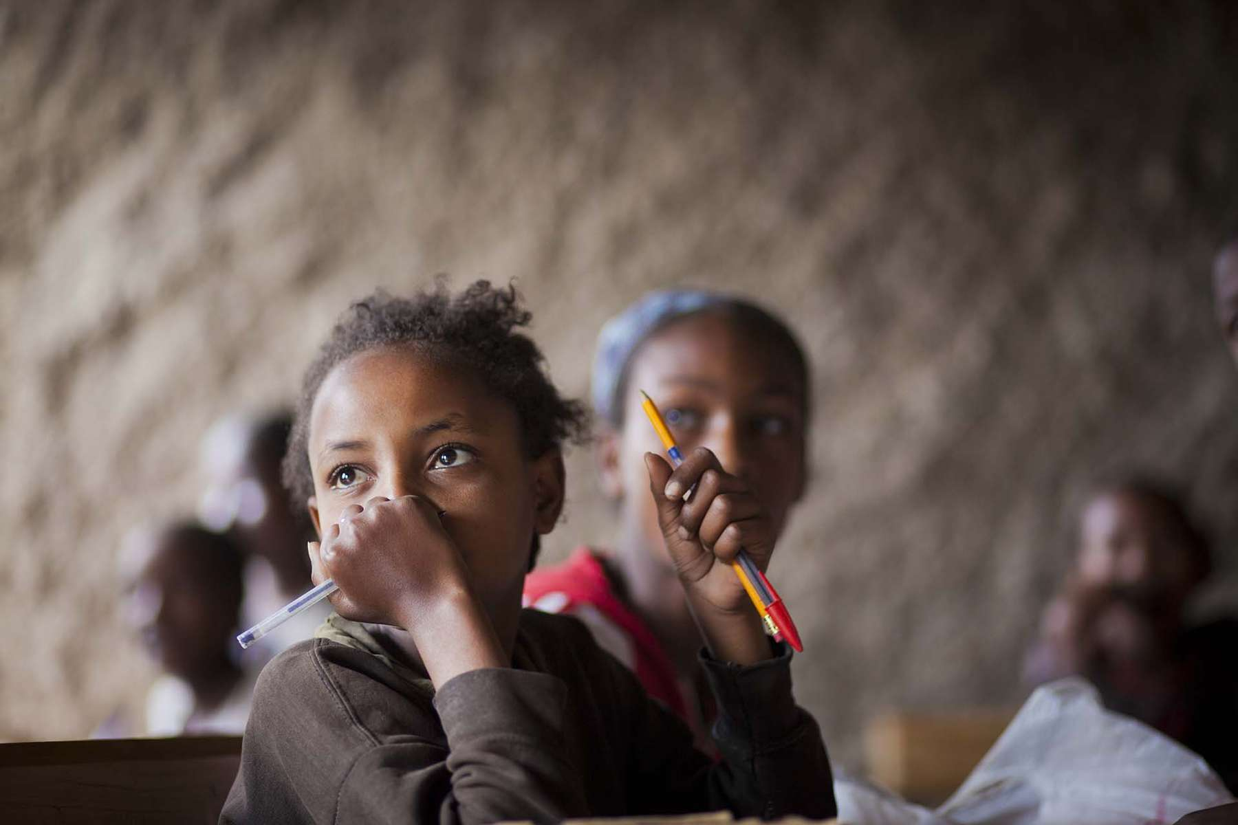 Bereket Brihanu, 11, listen to her teacher at Speed School class in Boricha in Oromia Region of Ethiopia November 29, 2011. Bereket, oldest of 3 siblings, dropped out of school at  2nd grade 2 years ago when her mother died. Her father is a laborer, and single income for the family could no longer afford 25 birr contribution fee for school (about 2 US dollars) and school supplies.  After her mother died, she was taking care of her baby brother at home. When she dropped out, she was not expecting to go back to school, started seeing herself as a mother of her younger brother. {quote}I was so happy to be back in school with children with my age, my friends,{quote} she said.  She wants to become a pilot because she once saw a female pilot on TV show.
