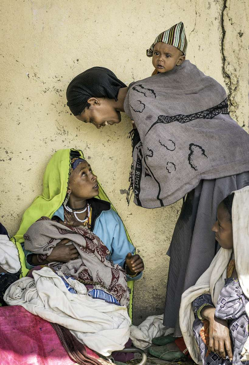 Mothers and their children wait for supplemental food prepared by a member of Health Development Army, a community volunteer group to promote better health practices, at a health post in the village of Dessie Zruia in Amhara Region of Ethiopia 8 October 2013.