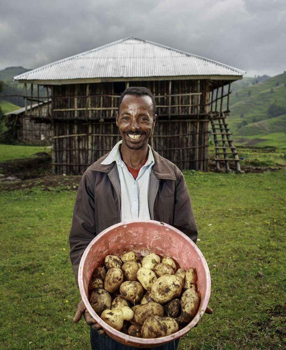 Seid Muhie, 30, father of 3 children, poses for a photo in front of his newly constructed house in the Village of Gelsha in Amhara region of Ethiopia 9 October 2013. Since he has started growing potato intrduced by Concern Worldwide, he has managed to build his own house with the extra income he has earned from the sale of potato.