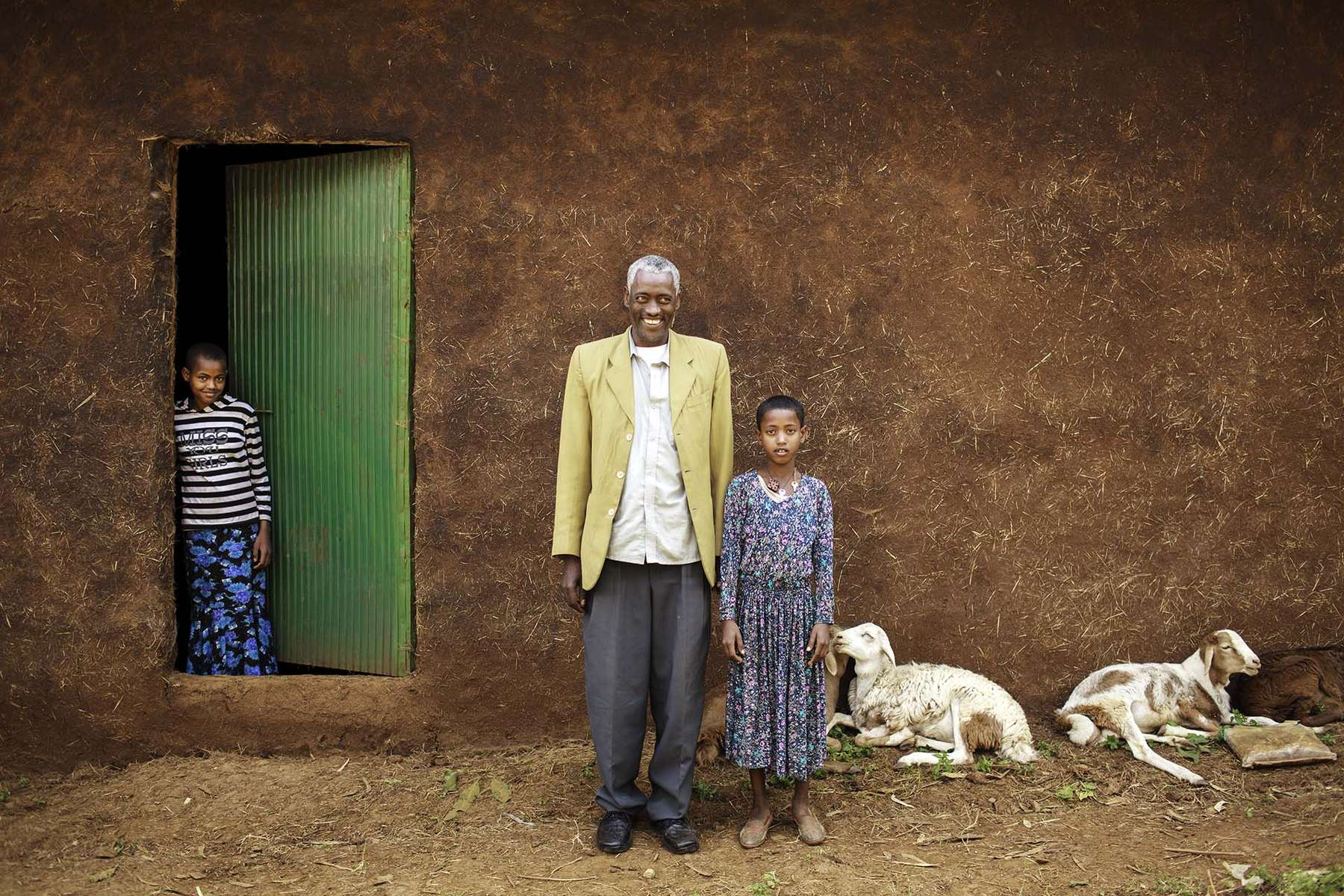 Negbaru Meheret, 42, poses for a photo with his daughters and newly-built warehouse in Womburma Village in Amhara region of Ethiopia January 21, 2011. He is a member Shindi Primary Cooperative. He used to sell his harvest at lower price, but now the cooperative pays the best price, and he has managed to earn enough money to build a new warehouse to store his harvest so he can sell it when the price is high. The cooperative participates in Purchase for Progress (P4P) by WFP. P4P in Ethiopia focuses on developing markets and helping farmers' cooperative members to produce more and market their crops so that they can engage more profitably and sustainably in markets.
