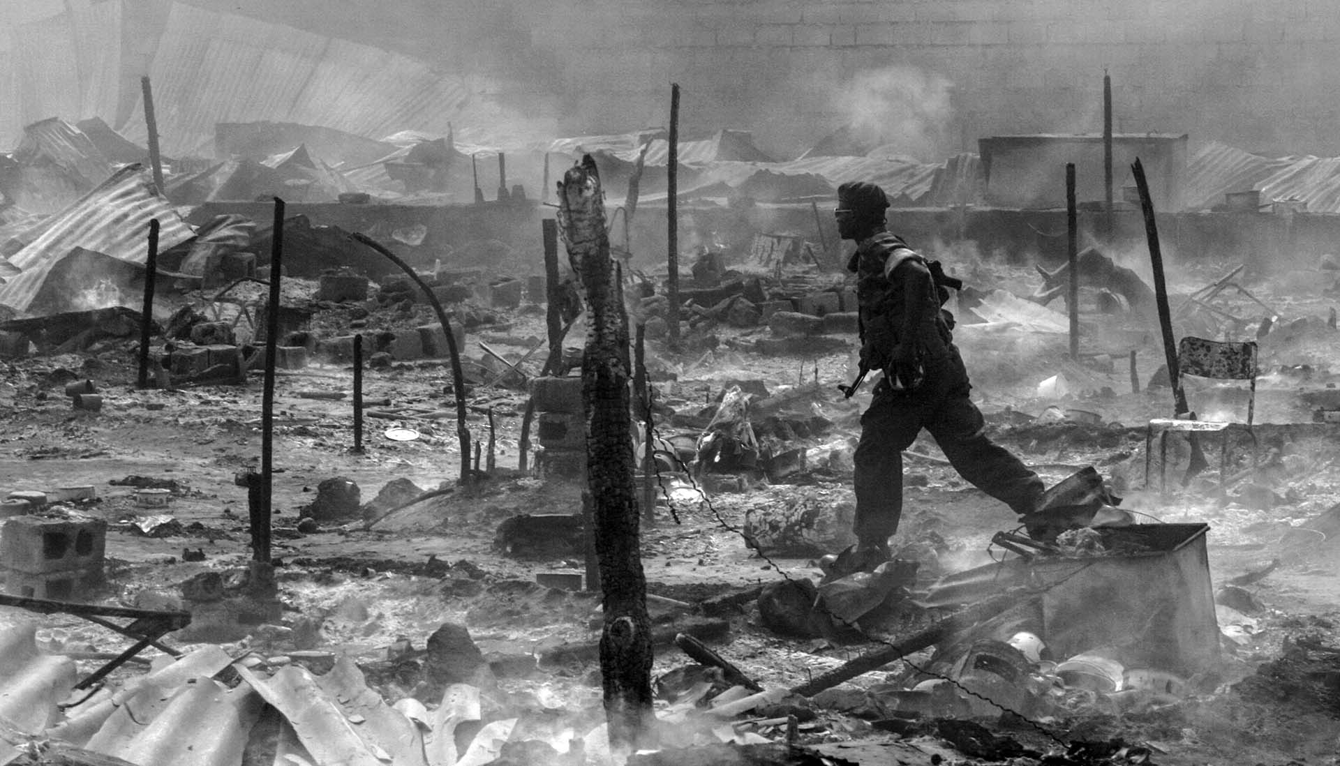 A soldier run through charred remains of the military barracks belong to the armed men belongs to Jean Pierre Bemba, presidential candiate, July 27 2006. Thus the tension is high in the capital ahead of the presidential election. Bemba accused Kabia of the arson of the camp.