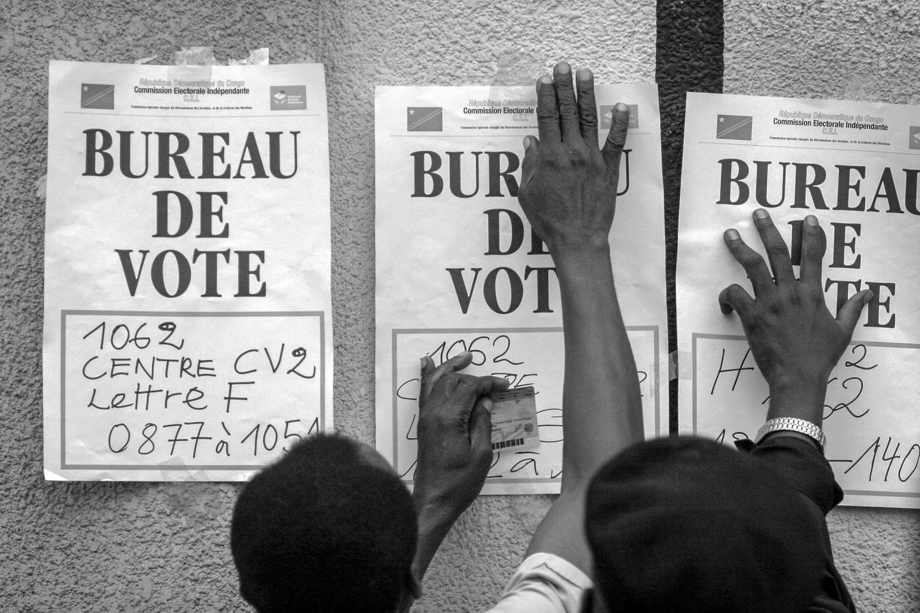 Election workers put up the sings at a polling station before it opens in Kinshasa. Voting took place without major violence as it was feared.