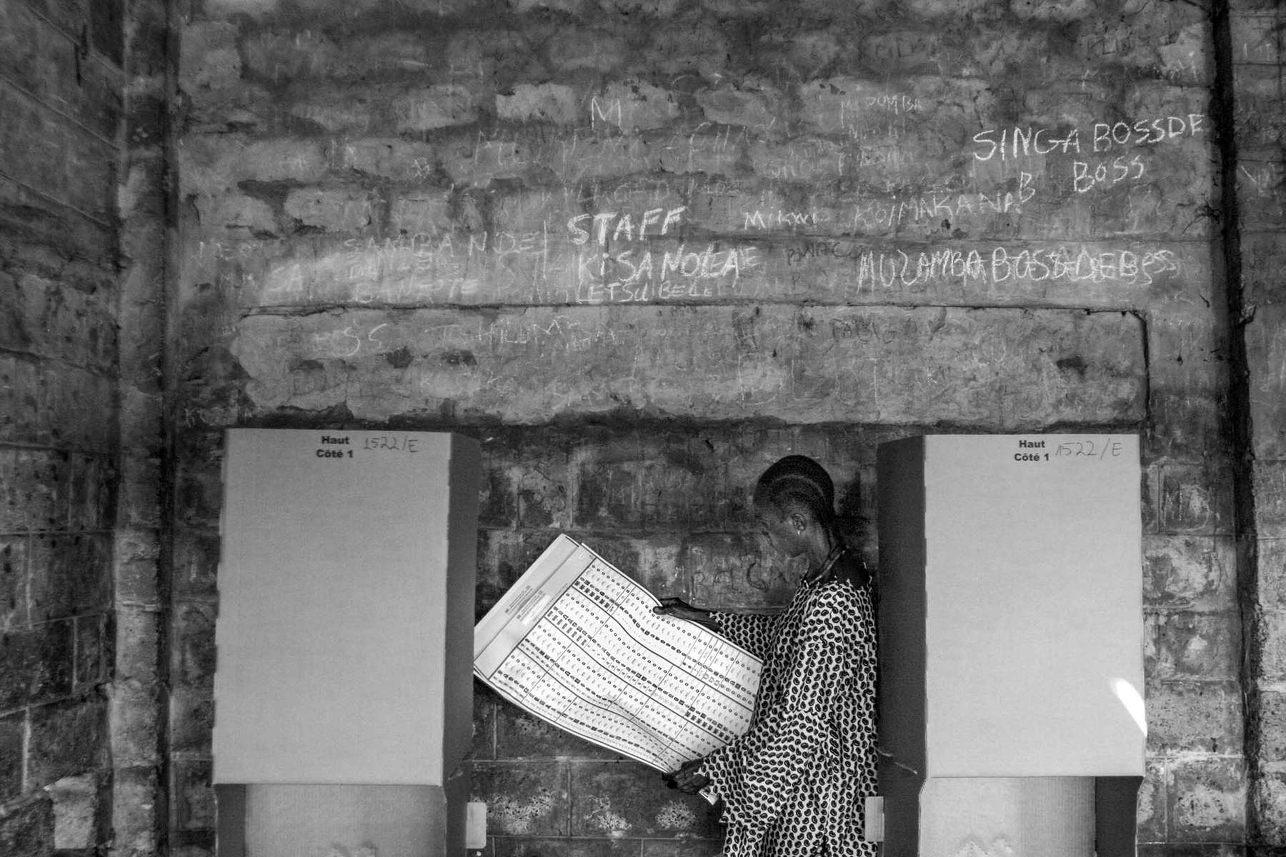 Congolese man studies 6-page-long ballot paper for legislative candidates at a polling station in Kinshasa.