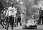 Supporter of UDPS, Congo's main opposition party which boycotted the upcoming Presidential and National election, confront riot police on the street of Kinshasa June 30, 2006, the nation's independence day.