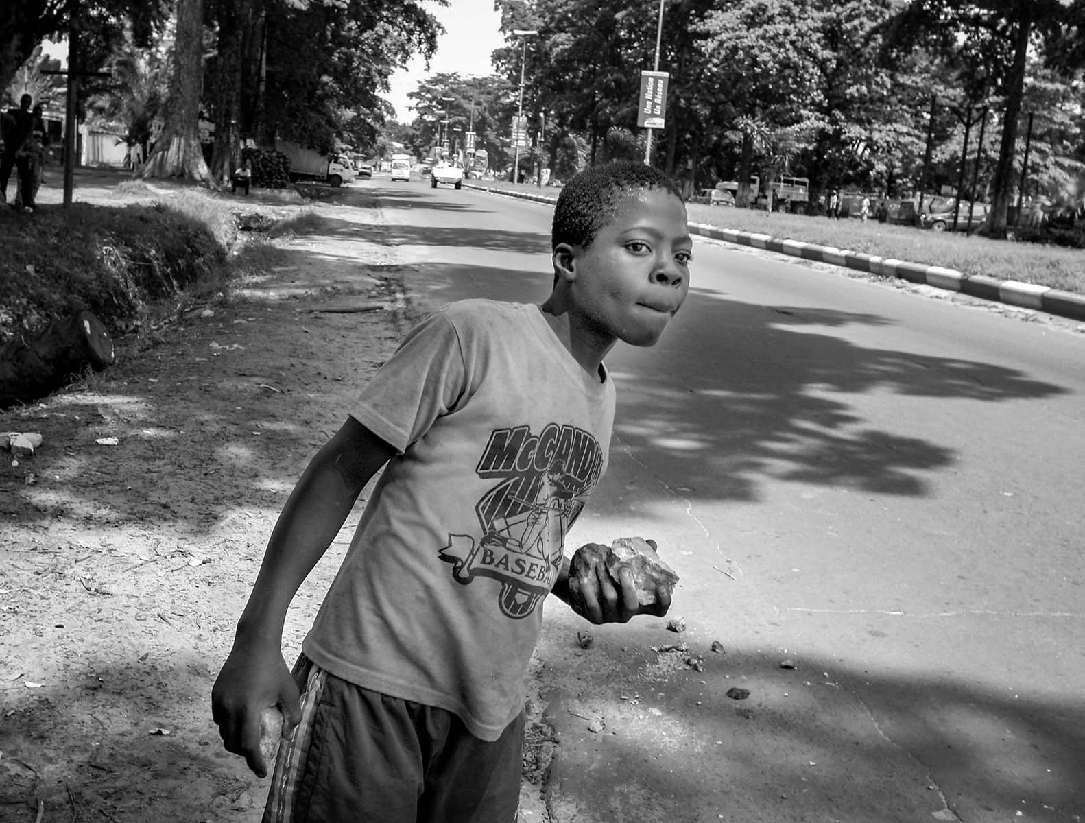 Young Congolese looks for an opportunity to throw his rocks at police on the main street of Kinshasa Thursday November 16, 2006. The day after Joseph Kabila was declared as the president, the air is tense in the capital.