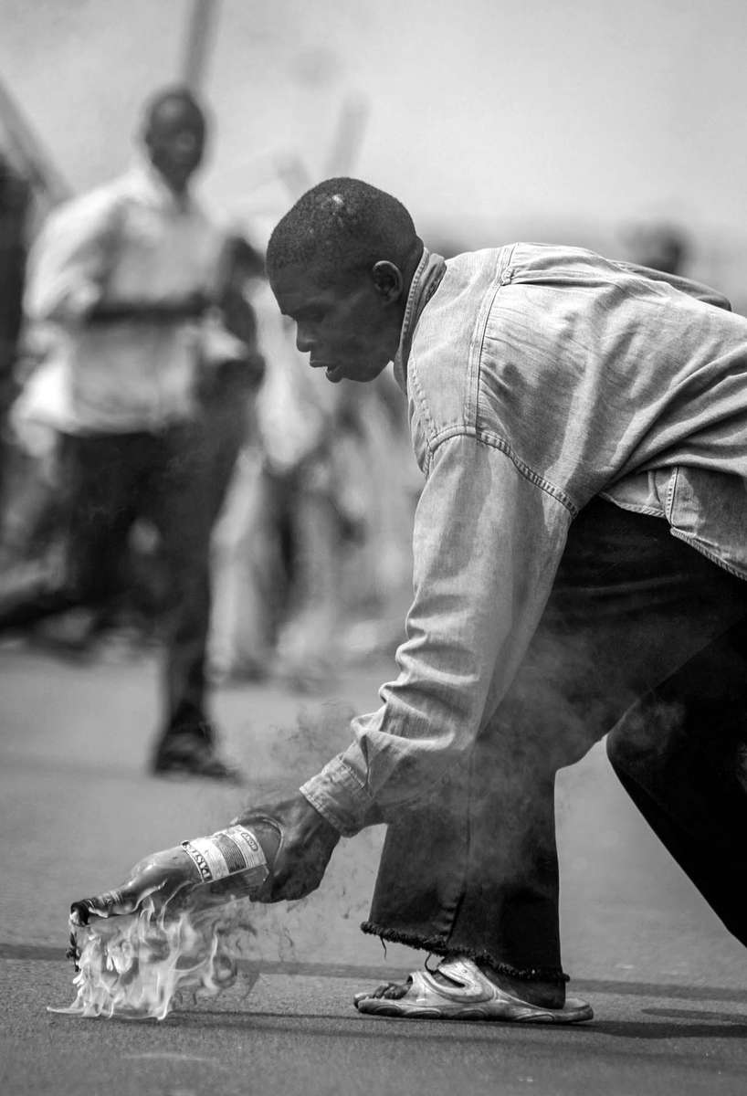 UDPS opposition supporters picks up an unexploded Molotov cocktail for the 2nd throw at riot police in Kinshasa.