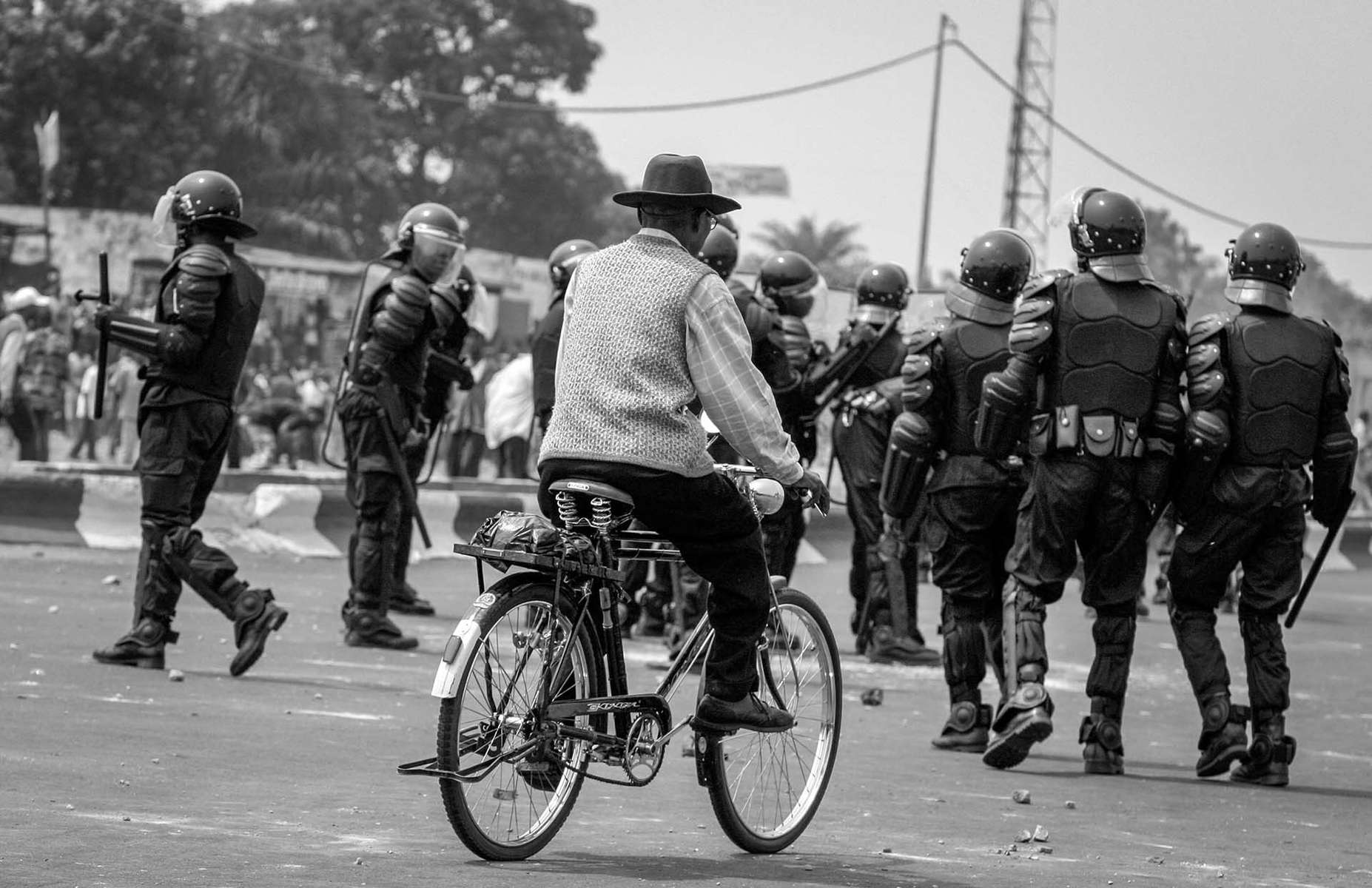 An old man cycles pass the riot police during the protest by UDPS in Kinshasa.