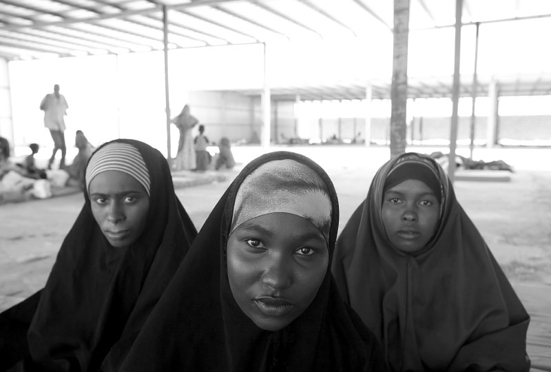 Refugees recuperate at a reception center in Ahwar a day after their arrival at the Yemeni coast from Somalia. Two sisters and a cousin traveled together from Mogadishu to Bosasso to Yemen. When they were thrown into the open water in total darkness of the moon-less night, they call each other to help each other stay alive. After the recovery, they will either try to find work in Yemen, the poorest nation in Middle East, or get smuggled into other countries, either options are difficult yet they prefer to leave it to their fate as long as they can escape the violence back in Somalia.