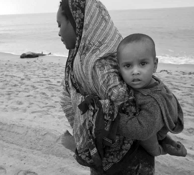 Fadua Ibrahim Haj Mohamed from Ethiopia walks along the beach she just reached in search of her older sister December 1, 2008 near the town of Afwar on Yemeni coast. She is carrying Riyadh Mukhter Sutlan 1 year and 5 month old son of her missing sister. After the search, she believed that her sister is dead. However Fozia Ahmed Hoshin, older sister, was later found in the water by NGO staff and rescued by a local fisherman, and being united later with her sister and son at the reception center. At least 20 people drowned off the coast of Yemen early Monday morning and two were reported missing after smugglers carrying them across the Gulf of Aden from Somalia forced them to jump overboard in deep water. The boat was reportedly carrying around 115 passengers.  UNHCR, UN Refugee agency in southern Yemen said 20 bodies were recovered and two people were missing and the remaining 93 passengers made it to shore after being forced overboard near a village outside the town of Ahwar, around 220 kms east of the Yemeni port city of Aden. Survivors were transferred to the UNHCR-run Ahwar reception centre. The dead were buried in a cemetery donated by the government of Yemen. The new arrivals received first aid, food and water on the shore and were then transferred to the reception centre to receive a complete medical examination by MSF and other assistance. More than 43,500 people in over 850 smuggling boats have arrived in Yemen so far this year after making the perilous voyage across the Gulf of Aden from Somalia. Most of those smuggled are Somalis. At least 380 people have died and some 360 are missing thus far. In 2007, some 29,500 people made the voyage to Yemen and the overall number of dead and missing reached 1,400.
