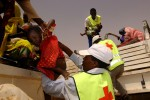 Red Cross workers help refugees get off transport trucks at a transfer center at Kashuni Refugee camp at Chad/Sudan border. Those who made it to the camp were the lucky ones. Millions were still in the area in Sudan where no aids are available.