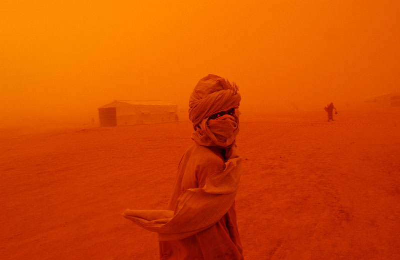 Young Sudanese boy makes his way through a mid-day sandstorm to a nearest cover at Kashuni Refugee camp at Chad/Sudan border.