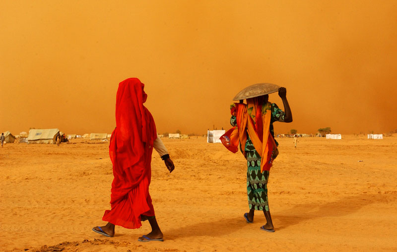 Sudanese women hurry their way to their tent as the wall of sandstorm approach the Kashuni Refugee camp at Chad/Sudan border.