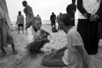 A Somali man offer his biscuit to anther refugee at the beach after landing.
