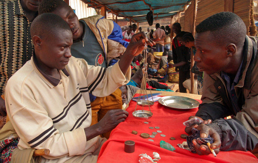 Fruit of labor is being measured by small coins and match sticks at a busy gold market in Iga-Barriere in Ituri.