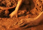 On hands and knees, muds and rocks are collected at the mines.