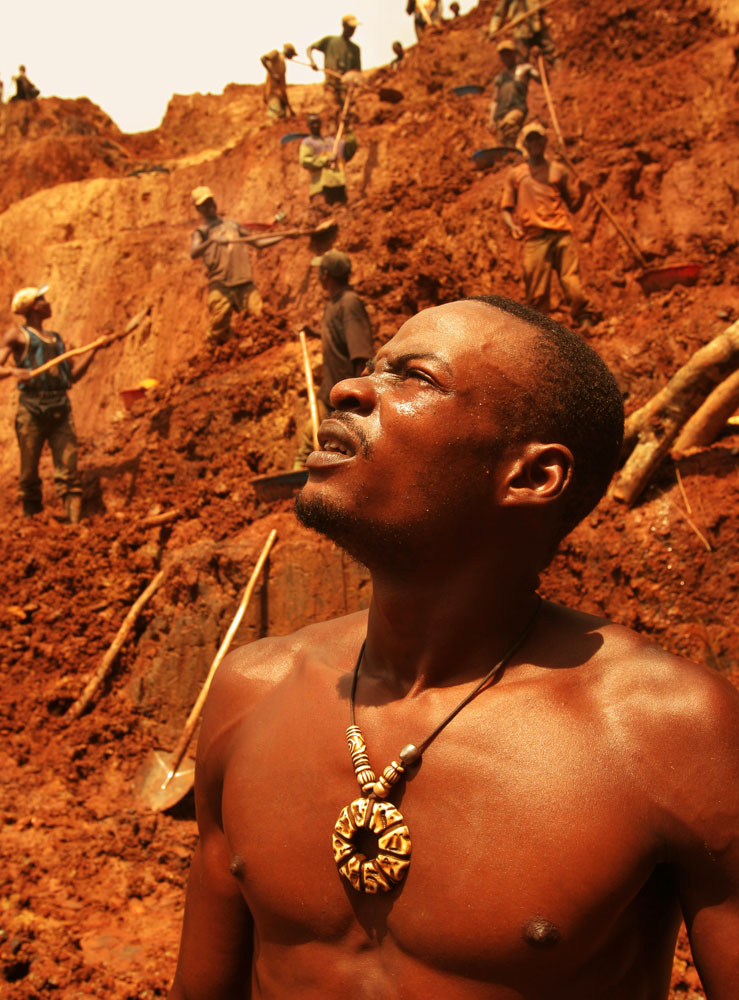 Congolese men takes a break from hard labor at an artisan gold mine in Montgbawalu. One man said people who work in the mines die young, too young.