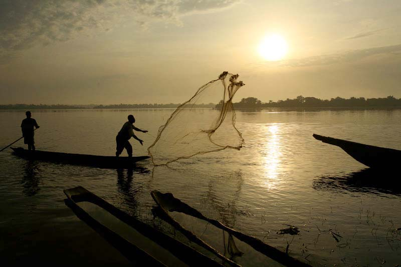 Fishermen cast their net on the Congo River in the village of Isangi in the early morning of March 23, 2007. Isangi is the hub of small communities surrounding the rainforest. Remote villages, such as Isangi, depend mostly on nature, the river and forest, for their survival.