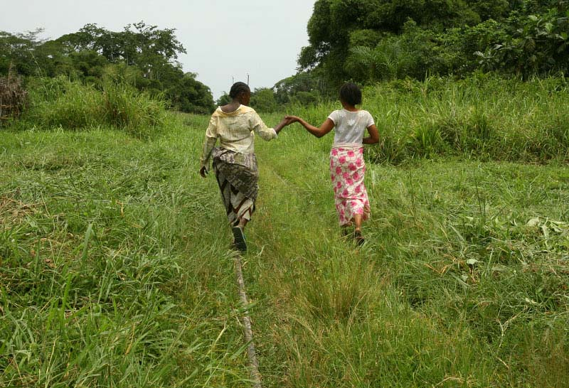 Congolese women try to keep each other's balanced as they walk on railroad tracks in Yoko National Reserve March 25, 2006. There has been recent crashed between local community and the Portuguese logging company which has somehow given a logging rights in the national park.