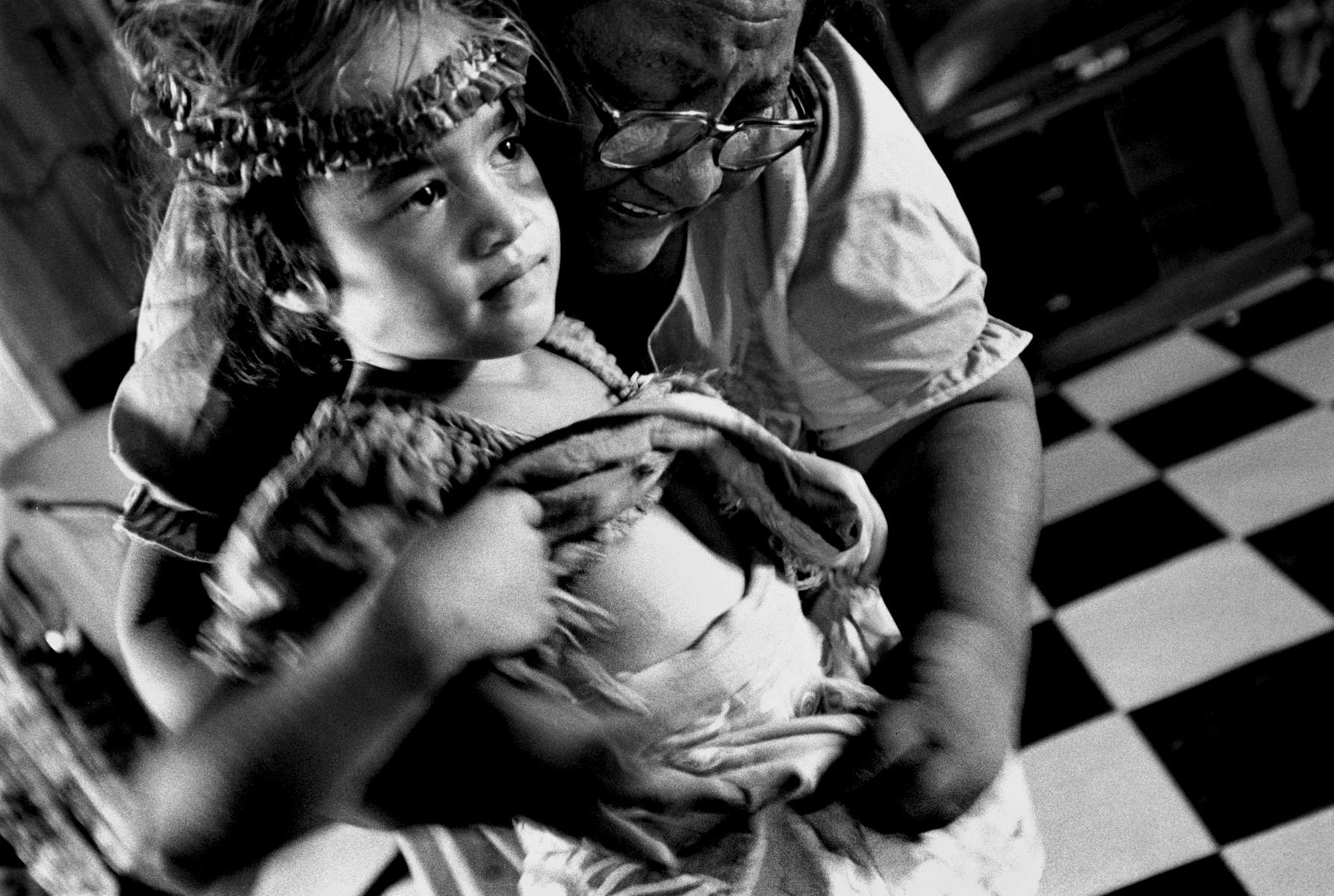 Grandmother helping her granddaughter get dressed for dance rehearsal, Nauru Island 2001