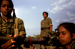 Female Tamil Tiger fighters during heavy weaponry training in the northern Vanni region of Sri Lanka. During a 6 month training period, the initial 3 months serve as an endurance testing ground beginning at 4:30 am until late evening. The training consists of long distance running, crawling under barbed wires, rope climbing, military parades coupled with theoretical and practical exercise with weapons, sentry posts staffed 24 hours, maintenance of the camp as well as political and military studies. The folowing 3 months is advanced military training with heavy weaponry and live ammunition - to familiarise both sound and impact.  Special training continues into areas of need, interest, and expertise in order to handle communication equipment, explosives, mining, weapon technology, electronics, field medecine, political work and intelligence/reconnaissance work. The women who show an aptitude for combat situations progress further to specialised commando training. 1998