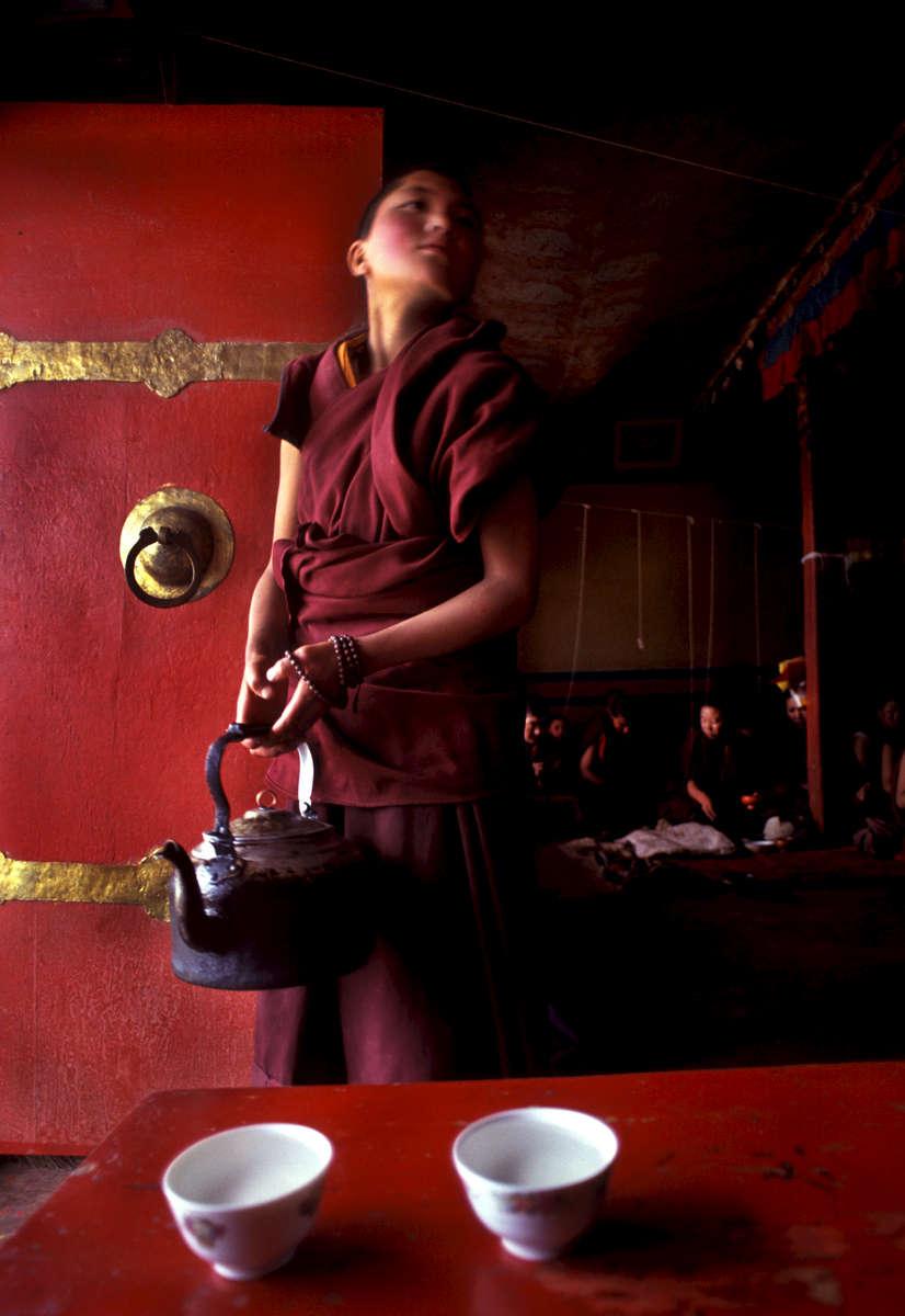 Tibetan nun serving yak butter tea during afternoon prayer at Chusang monastery, Tibet 1992