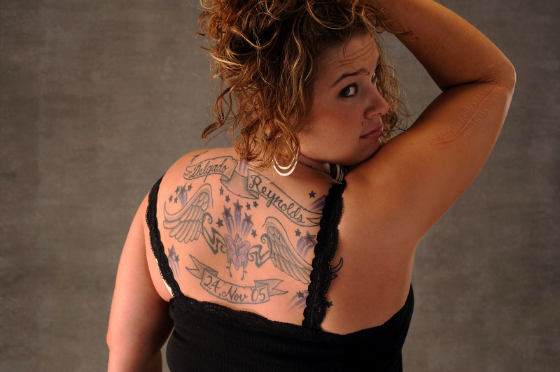 Melissa with her fallen fellow soldiers names tatooed on her back.