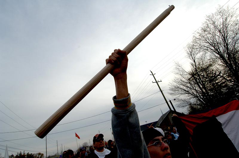 A protestor brandishes a weapon.