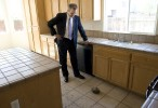 Real estate agent Mike Blower inspects damage in an abandoned forclosed property in Stockton, CA.