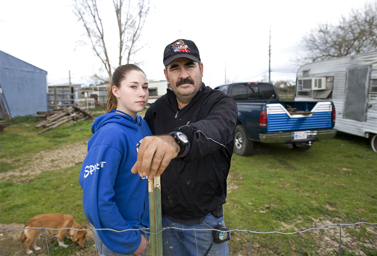 Elmer Hibbar, 51, and his daughter Willow, 14, on their farm property near Orland, California. Hibbar, who is on a fixed disability income, says it is becoming harder and harder to make ends meet. {quote}The dollar just doesn't go as far as it use to.{quote}