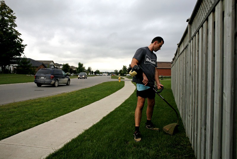 Frank Farbas trims some weeds on the property he owns bordering the disputed territory.