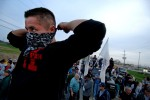 A Six Nations warrior stands on a barricade after police attempt to break up a group of protestors occupying a disputed land tract.