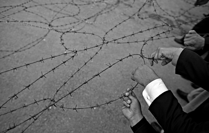 Pakistani lawyers try to remove a barbwire barricade with their bare hands.
