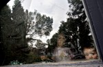 Children look through the broken window of a North Central residence during a housing standards inspection.