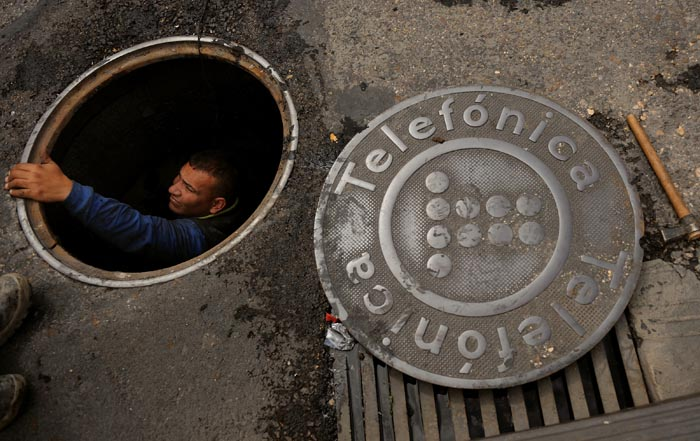 Telefonica employee Luis Salfredo comes out of a manhole while repairiing telephone lines on Thursday May 13, 2010 in Madrid, Spain. Photographer: Denis Doyle)