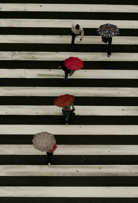 People cross the Gran Via on October 20, 2006 during a rainy day in Madrid, Spain.