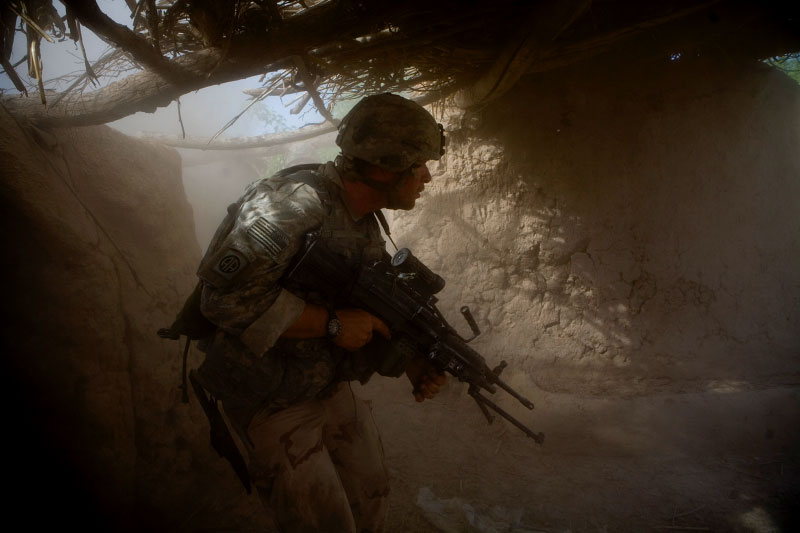 Private Dan Burris of the 82nd Airborne searches a compound through the dust and smoke of a grenade.