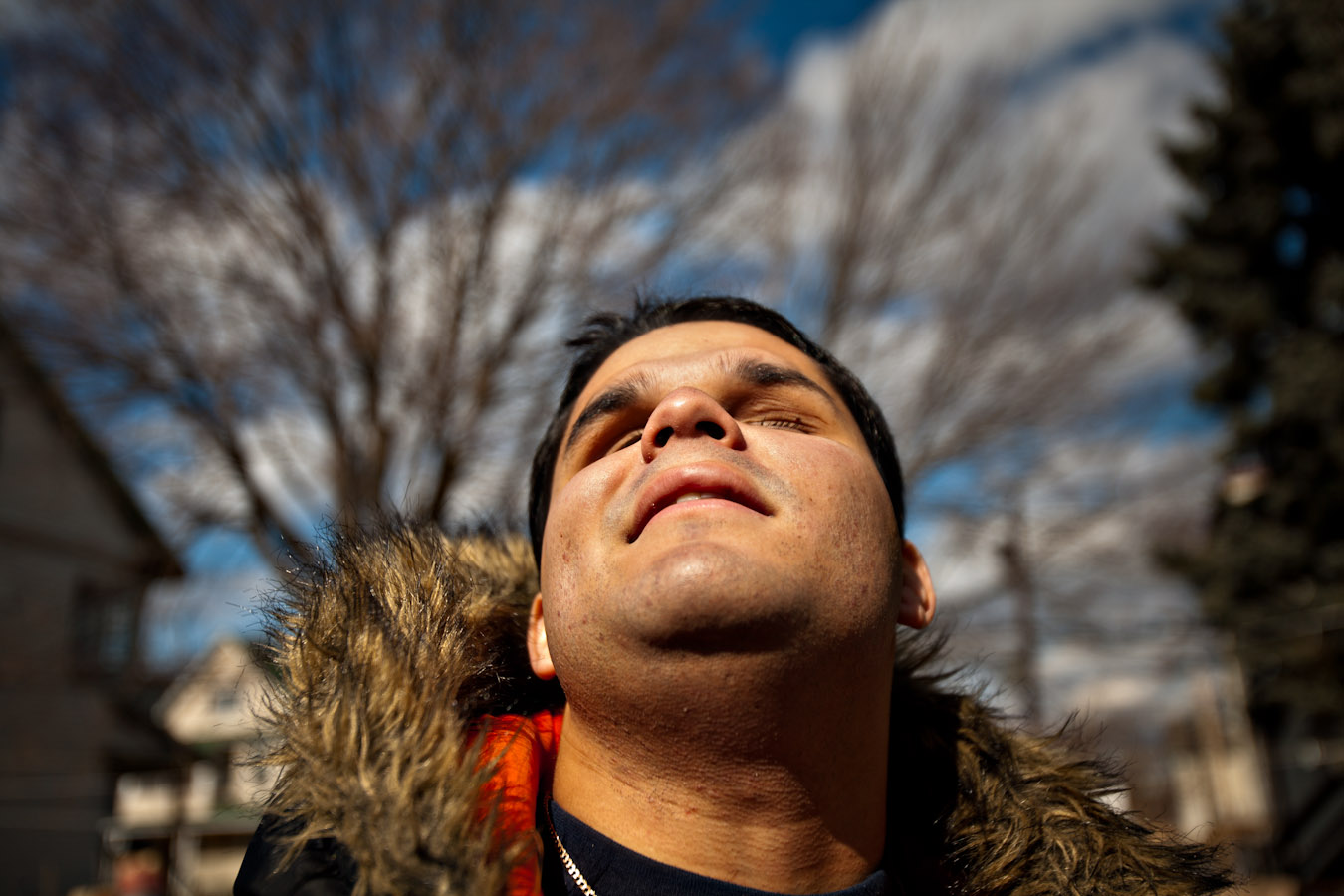Hector raises his face toward the afternoon sun while waiting for his mobility instructor on a cold winter day in Bridgeport, Conn. Hector works with his trainer on strengthening his ability to travel independently using a cane and his other senses.