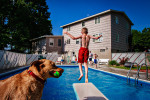 Chris Dietrich bounces from the diving board while his Golden Retriever, Cali, races to meet him in the pool on an July afternoon in Syracuse, New York.Photograph by Jesse Neider