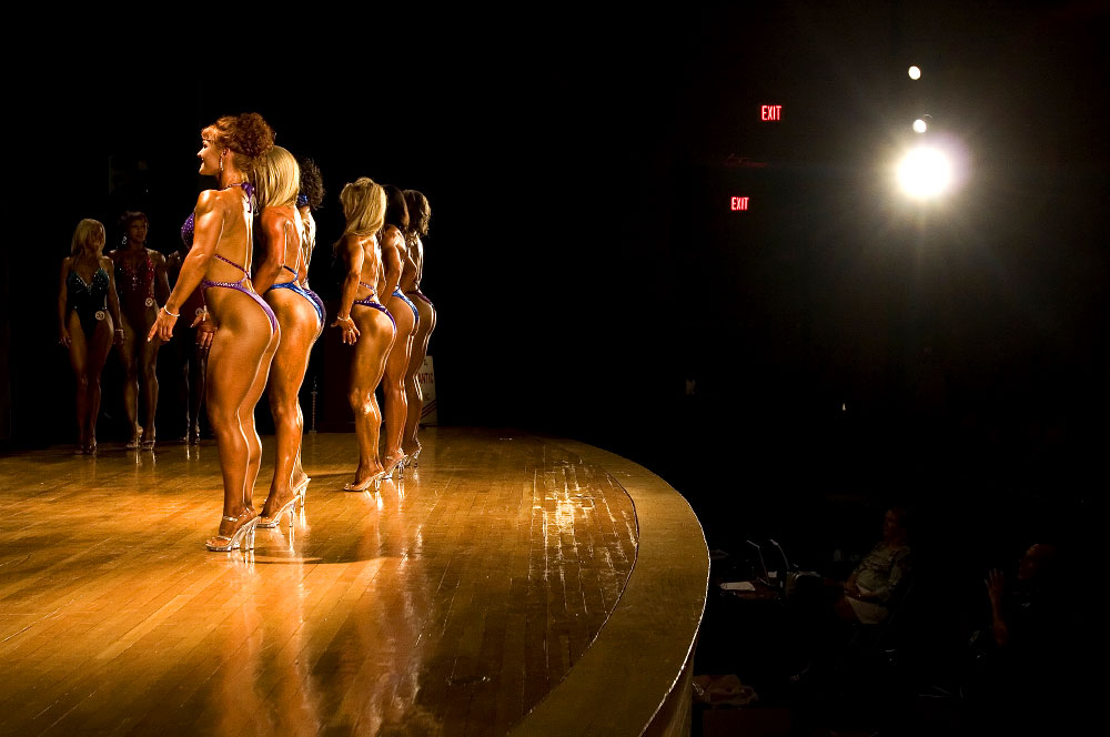 Woman competing in the Potomac Cup bodybuilding competition in Woodbridge, VA line the stage to show off their toned bodies for the judges.
