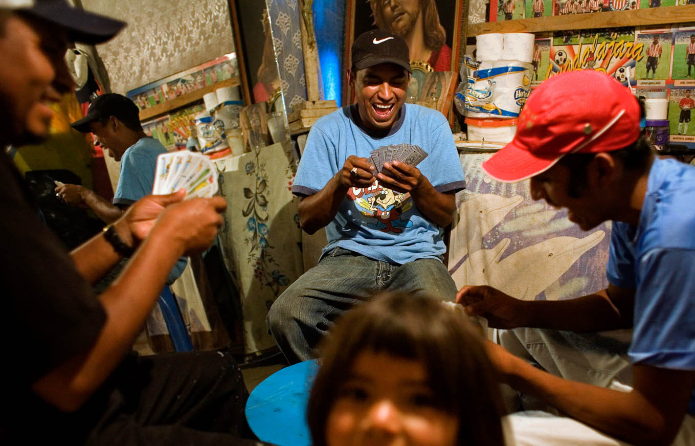 Angel Andres laughs while taking the afternoon off from scavenging in La Neza, a private dumpsite outside of Mexico City, to play cards with his friends in his family's makeshift home.