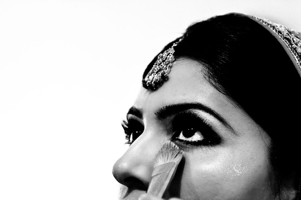 An Indian bride has her makeup touched up before her wedding ceremony.