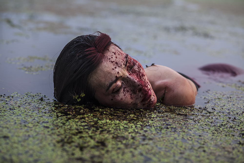 Beijing, Aug.4, 2018  performance artist Han Bing acts during an art project in a polluted lake on the outskirts of Beijing.