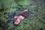 Beijing, July 30 : performance artist Han Bing lies in a polluted lake during an art project in a polluted lake on the outskirts of Beijing.