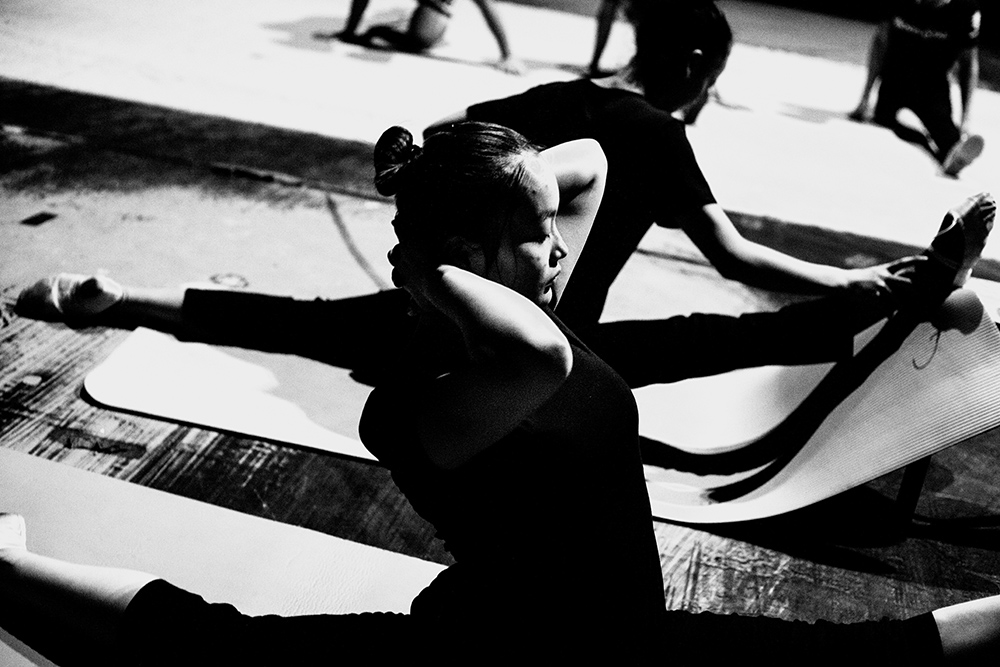 A young performer stretches during rehearsals for a show in Beijing
